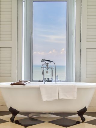 Luxury bathtub with relaxing ambient window with scenic sea vie